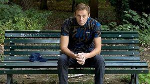 Aleksej Navalnyj sitter på en parkbänk iklädd sportskjorta.