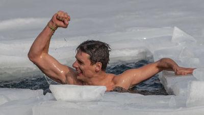 En glad man i en isvak höjer armen och näven i en segergest.