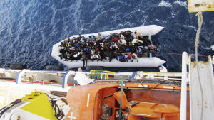 on 20 April 2015 shows a boat with refugees next to the cargo ship 'OOC Cougar' in the Mediterranean sea on 05 February 2015. The ships of the German shipping company Opielok Offshore Carriers have rescued more than 1,500 people in the Mediterranean sea s