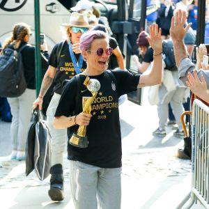 Megan Rapinoe går med pokalen och gör High-five