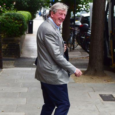 En skrattande Roy Hodgson i grå kavaj promenerar på en gata.