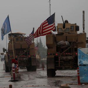 Amerikansk militärkonvoj vid vägspärr i dimmigt Syrien.