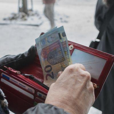 Rahapussi ja seteleitä naisen kädessä.
