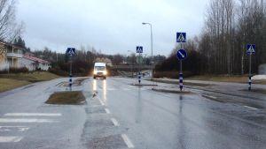 En asfaltväg där en vit skåpbil närmar sig en korsning, övergångsställe, det regnar.