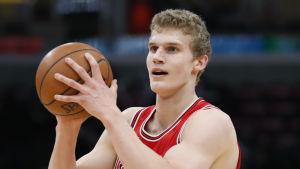Lauri Markkanen med en basketboll i händerna.