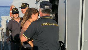 Kaptenen Carola Rackete eskorteras av polisen från Lampedusa till staden Agrigento där hon ställs inför domstol..