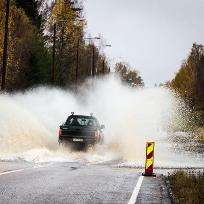 Bil kör på översvämmad väg