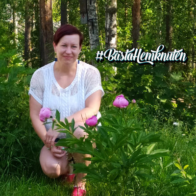 Anna sitter i trädgård med ljusröda pioner framför sig.