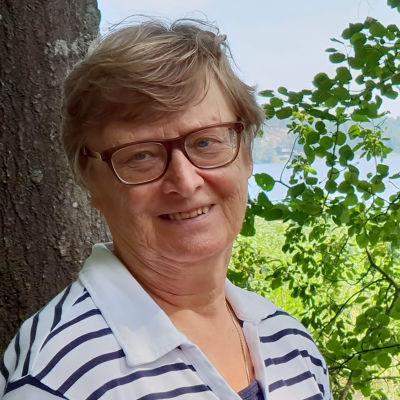 Äldre kvinna i glasögon står invid två träd vid stranden.