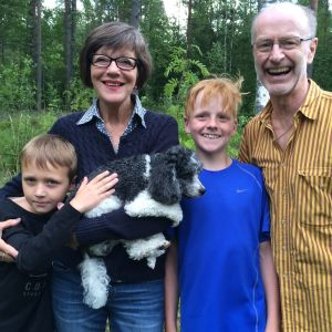 Jaakko ja Hannele lastenlastensa ja koiransa kanssa omalla kotipihalla. Lastenlapset ovat Jaakolle todella tärkeitä ja tuovat täyteyttä elämään.