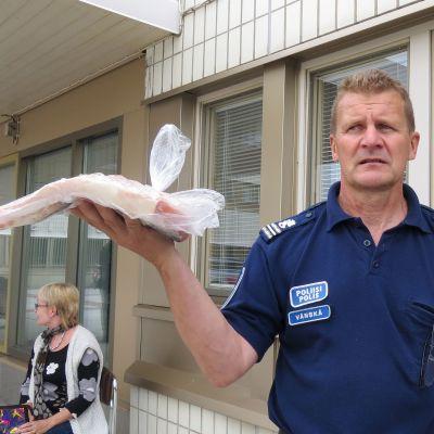 Komisario Eero Vänskä huutokauppaa laittomasti pyydettyä lohta Kemin poliisiaseman pihalla.