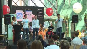 John Smeds, Kaj Smeds och Oscar Löfqvist står på en scen inför publik på suomiareena.