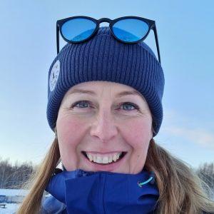 En leende kvinna ser in i kameran. Hon är utomhus, i bakgrunden syns snö.