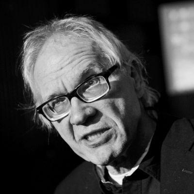 Svartvit bild av Lars Vilks som pratar och tittar framåt.