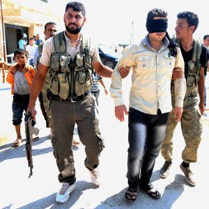 Bild på två män i militär utrustning som gripit en man i vit skjorta och ögonbindel.