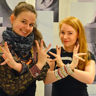 Suvi Tuominen och Mikaela Jokinen visar en traditionell handrörelse från den indiska dansen.