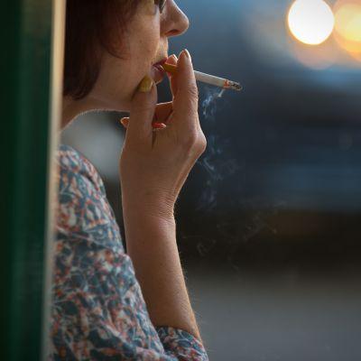 Nainen polttaa tupakkaa.