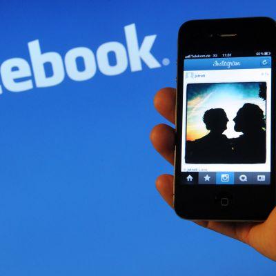 Kuvassa iPhone-kännykkä ja takana lukee Facebook.