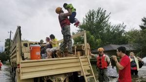Människor som bor i ett översvämmat område räddas av Texas nationalgard.