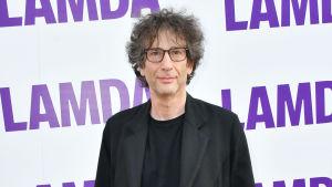 Neil Gaiman klädd i svarta kläder. Står framför en vägg som det står LAMDA på.