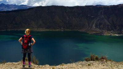 Kvinna står och ser ut över en vulkan