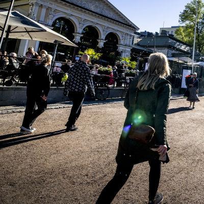 Människor går längs med sandvägen på Esplanadparken i Helsingfors. Solen skiner.