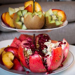 Hedelmälautanen, jossa kiwi, granaattiomena ja persikka