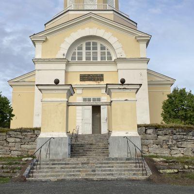 Keminmaan uusi kirkko pylväsporttien ulkopuolelta kuvattuna. Uusitut portaat johtavat pihalta kirkkoon, jonka ovi on auki.