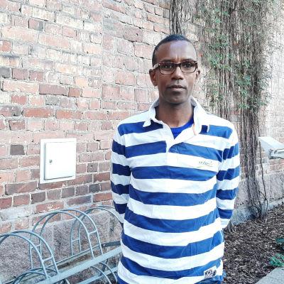 Tariku Ahlfors, med mörkt hår och glasögon, står framför en vägg av tegelstenar. Han har på sig en vit- och blårandig skjorta.