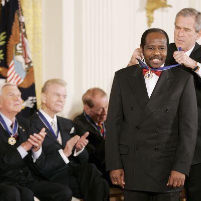 George W. Bush ripustaa Yhdysvaltain presidentin vapaudenmitalin Paul Rusesabaginan kaulaan.