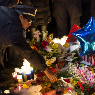 En polis lämnar blommor på minnesplatsen för de två poliserna som dödades i New York.