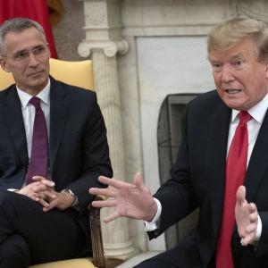 Donald Trump använder händerna för att förklara något för pressen och Jens Stoltenberg som lyssnar vid sidan i Ovala rummet.