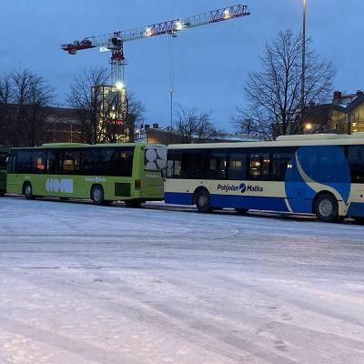 Kuvassa linja-autoja jonossa lumisella torilla