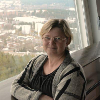 Tiina Heinonen seisoo Puijon tornin kahvilassa Kuopio taustallaan.