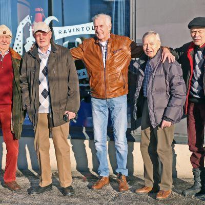 Viisi vanhaa miestä seisoo ravintolan edustalla kädet toistensa harteilla