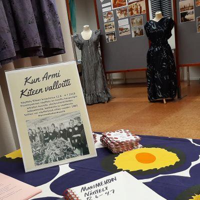 Kaksi Marimekon mekkoa taustalla, edessä pöytä, jossa näyttelyesite ja vieraskirja.
