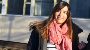En kvinna i långt brunt hår och randig tröja. Solen lyser i ansiktet och hon ler.