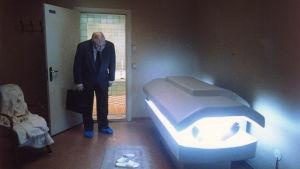 en man i kostym lutar sig över ett solarium ur vilket en mans bara fötter sticker fram.