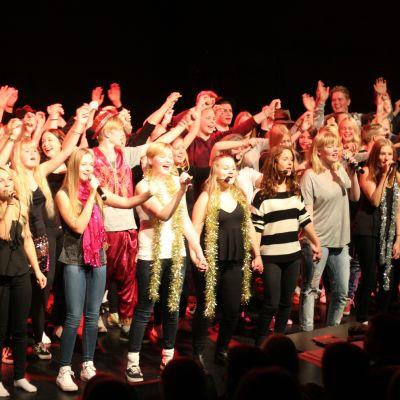 Ungdomar står på scen och sjunger.
