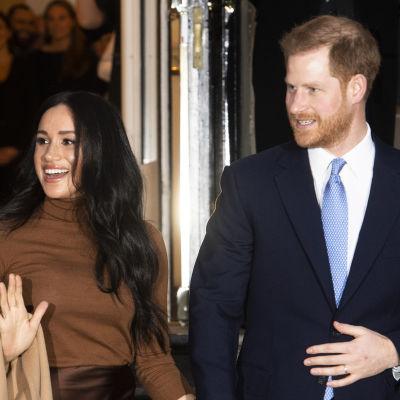 Meghan vinkar och Harry håller henne i handen.