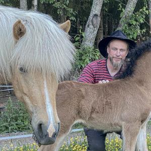 Juha Suonpää Anniston pihalla hevosten kanssa.