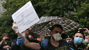 En man under paraply håller en skylt, poliser i bakgrunden fattar tag om honom.