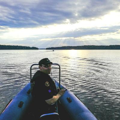 Sjöbevakare Juha Martiskainen sitter i fören i en båt.