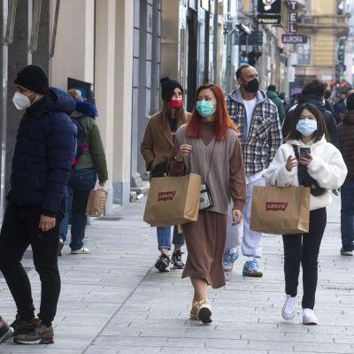Personer går på en shoppinggata i Italien, iklädda munskydd.