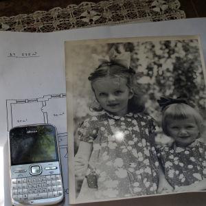 En gammal mobiltelefon och en gammal bild på systrarna.