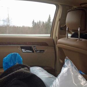 Auton takapenkillä otettu kuva niin että siniseen sairaalatossuun puettu jalka näkyy tyynyjen päällä, vasemman puoleinen sivu-ikkuna taustalla. Vanhempi nainen ajaa autoa.