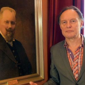 Konstnären Peik Bäckström står bredvid porträttet av borgmästare Harry Winqvist.