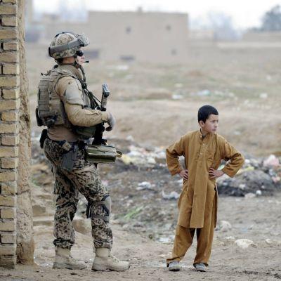 Soldat och pojke står bredvid varande.