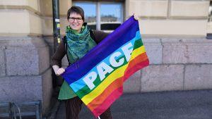 Minerva håller i en regnbågsflagga med det italienska ordet pace på