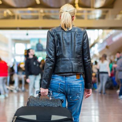 kvinna står på terminal med ryggen mot kameran.